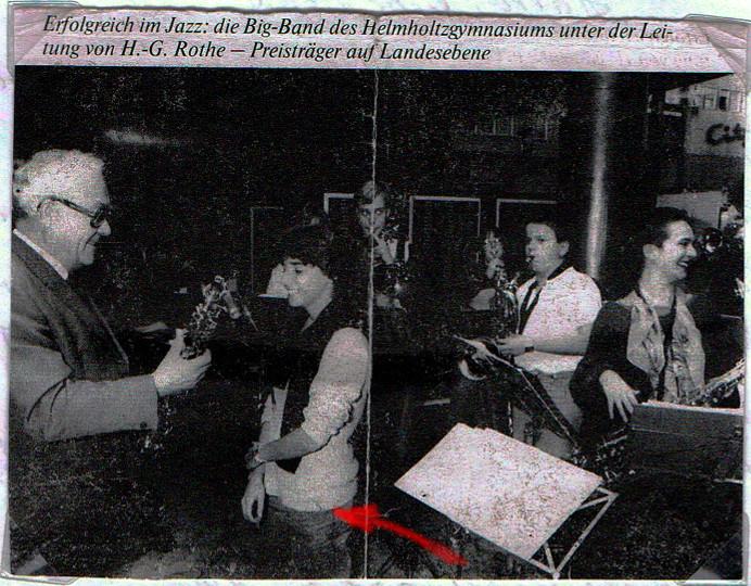 Übergabe eines Alt-Saxophons an Anja Sachs, im Hintergrund mehrere Musiker der BigBand des Helmholtzgymnasiums Karlsruhe
