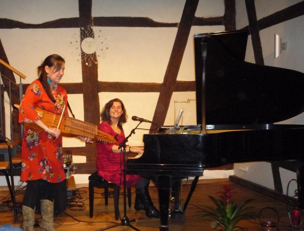 Liedermacherin Anja Sachs am Flügel und Geigerin Sue Ferrers stehend mit Nyckelharpa