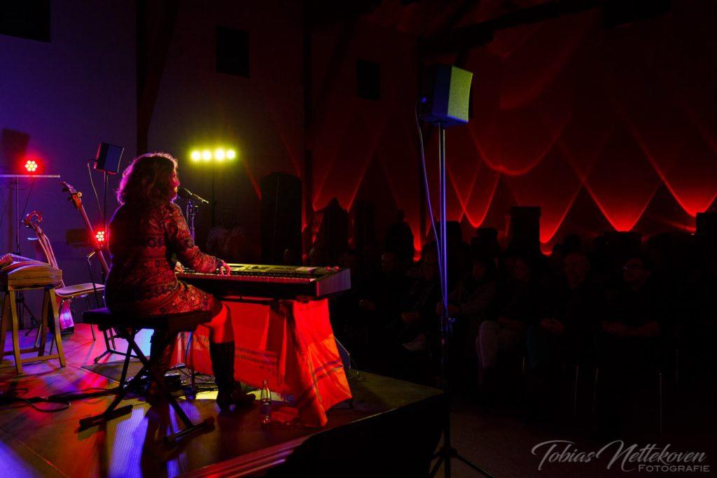 Liedermacherin Anja Sachs am Keyboard im roten Bühnenlicht, Bühnenperspektive von hinten