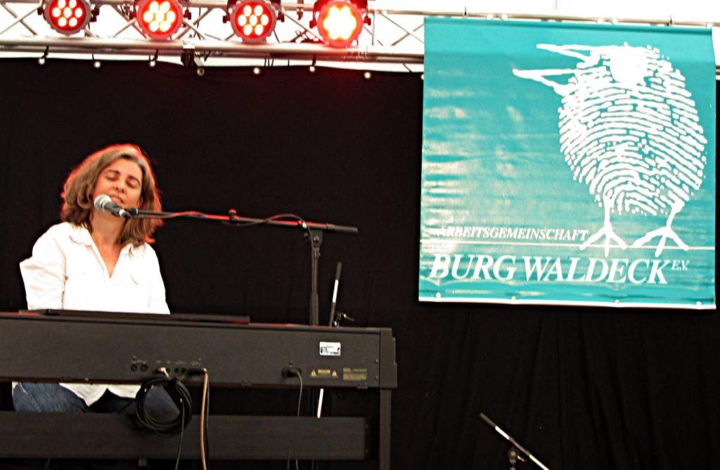 Liedermacherin Anja Sachs am Keyboard, im Hitergrund das Banner des Liederfests Burg Waldeck 2018