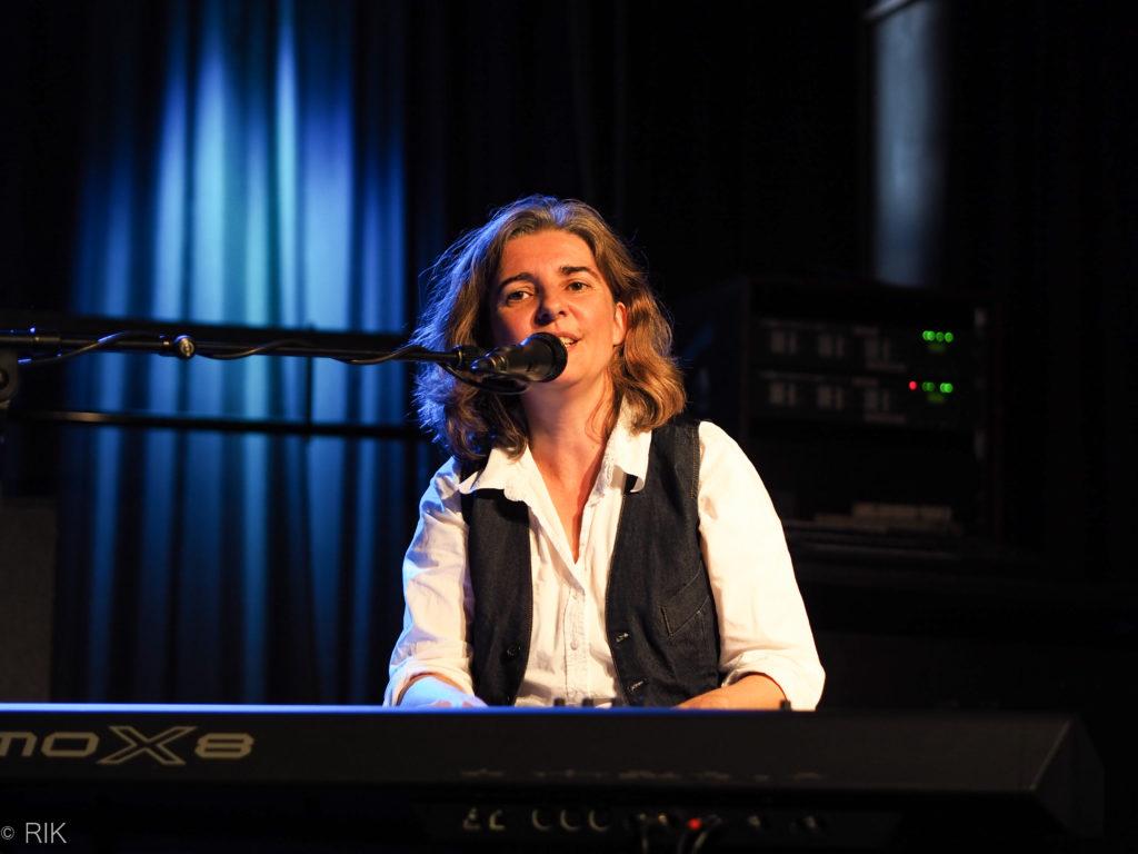 Liedermacherin Anja Sachs am Keyboard im blauen Bühnenlicht