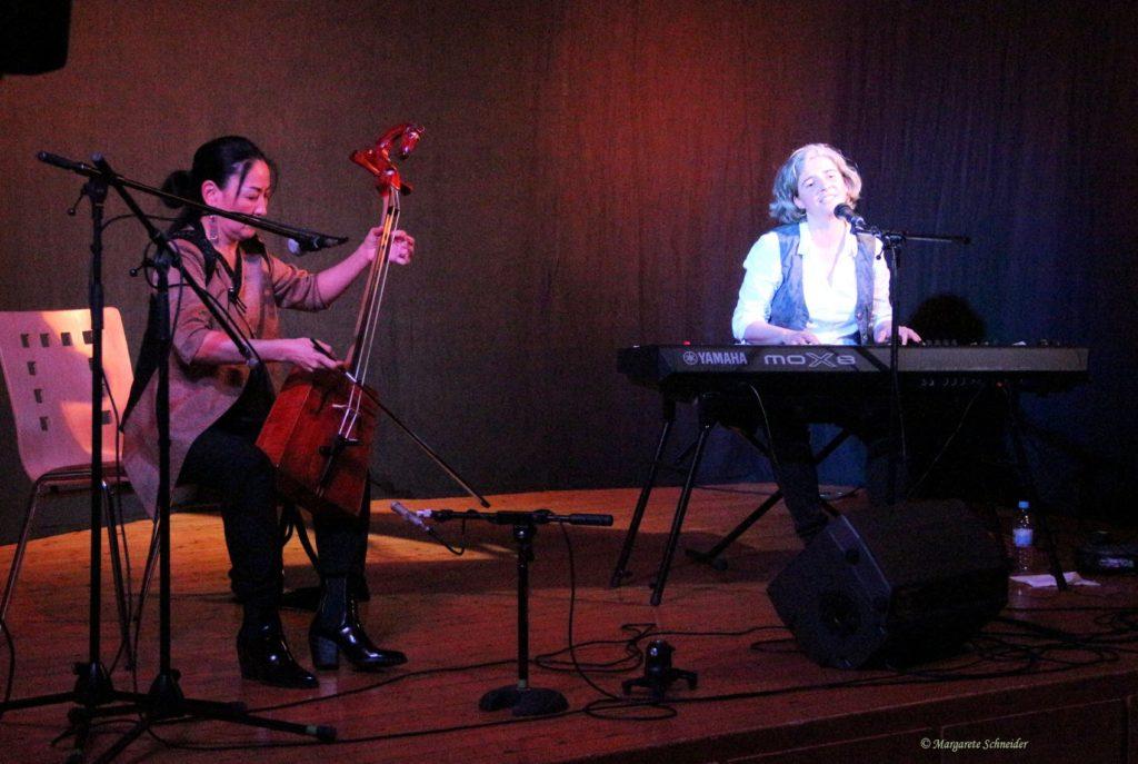 Die mongolische Weltmusikerin Enkthuya Jambaldorj mit Pferdekopfgeige und die Liedermacherin Anja Sachs am Keyboard nebeneinander auf der Bühne