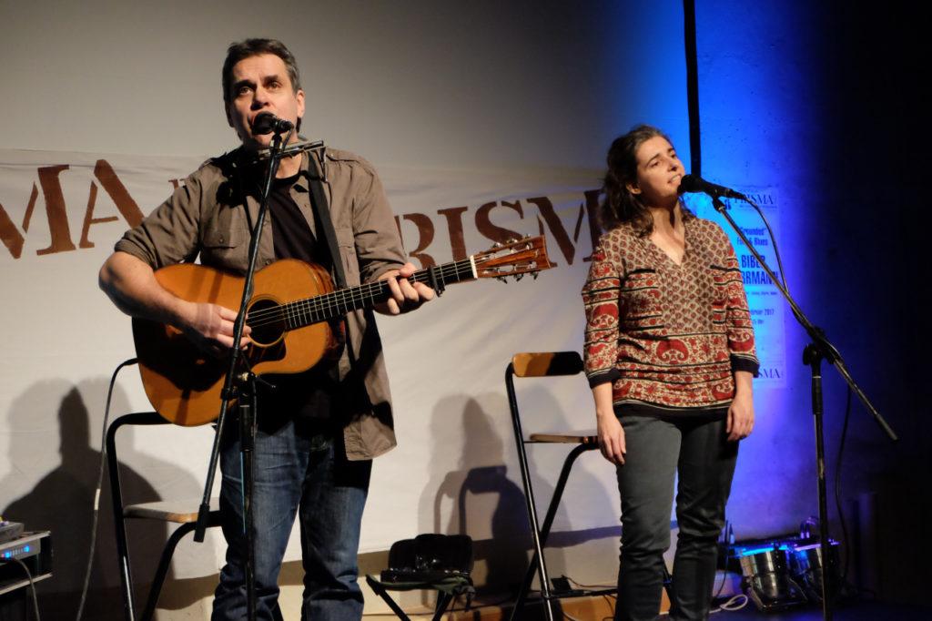Biber Herrmann mit Gitarre neben Anja Sachs, beide stehen singend vor zwei Mikrofonen